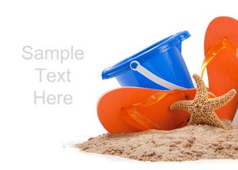 Beach scene with flipflops, sand, bucket and starfish