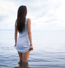 Young and sexy lady in a dress standing in the water