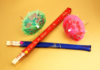 two sets of colorful chopsticks on gold decorated