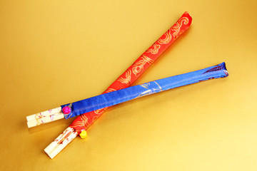 two sets of colorful chopsticks on gold