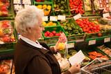 Fototapety Seniorin beim Einkaufen von Lebensmittel im Supermarkt
