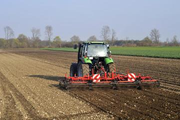 Bauer mit Traktor auf Feld im Frühjahr
