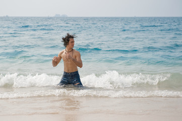 Athletic man in the Pacific ocean shaking his wet hair.