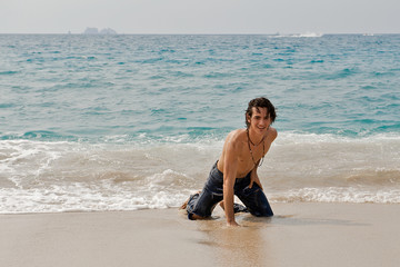 Athletic young man on the beach in the ocean waves.