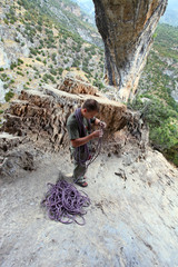 Rock climber winding a rope after ascent