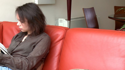 Intellectual woman reading a magazine sitting on sofa
