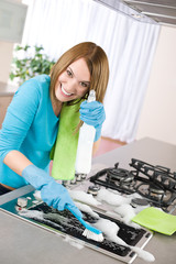 Young woman cleaning stove in kitchen