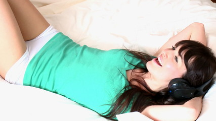 Delighted woman listening music with headphones lying on her bed