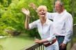 Glückliches Älteres Paar auf Brücke winkt zum Abschied