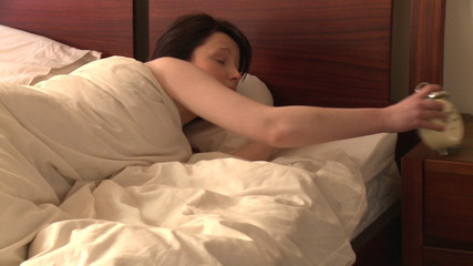 Brunette woman waking up and looking at alarm clock