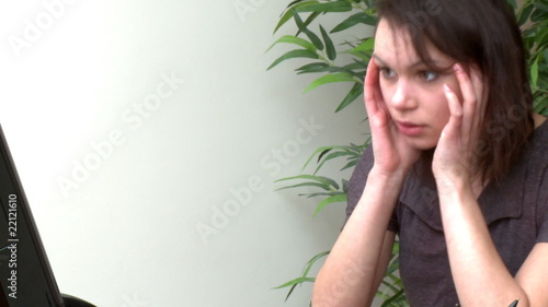 Upset woman working at a computer at home