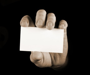 Hand with business card on black background