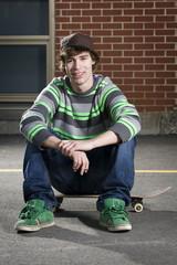 Skateboarder sitting on board