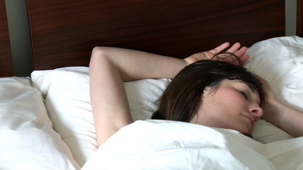 Dreamy woman sleeping on bed at home