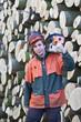 Waldarbeiter mit Kettensäge vor Buchenholz