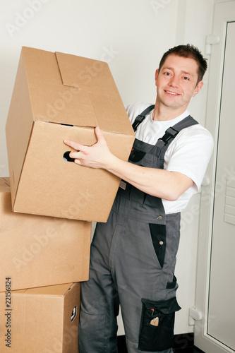 Möbelpacker beim Umzug hebt Umzugskartons