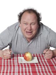 homme obèse mangeant une pomme régime