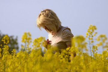 Ragazza bionda pensierosa in un campo di colza in fioritura