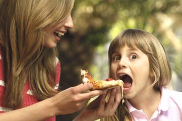 madre che imbocca la figlia con un pezzo di pizza