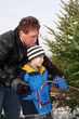 Man cutting a Christmas Tree with his son