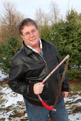 Man holding a saw on a Christmas tree farm