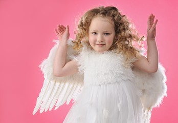 Beautiful little angel girl isolated on pink background .