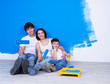 Smiling family with paintbrush near the wall