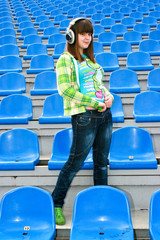 Teen at the stadium with earphones listening music