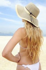 elegant woman with long blond hair at the beach, rear view