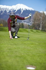 Woman golfer aligning golf ball to a hole on a putting green