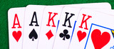 Full house of aces and kings on green