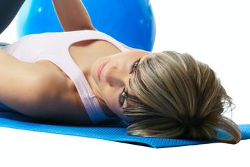 Sportswoman lying on a mat.