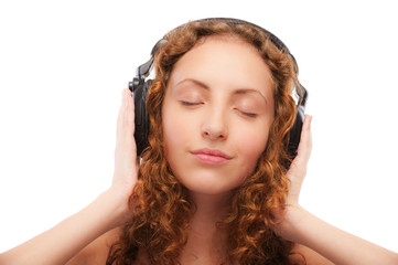 Beautiful curly girl listens to music through ear-phones