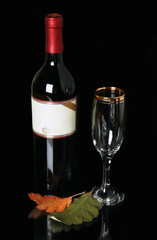 Bottle red blame with empty label and goblet on black