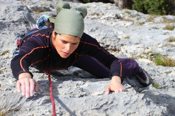 Rock climbing. Young woman climbing a limestone rock