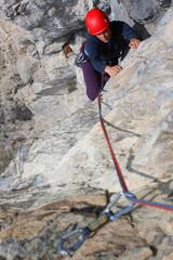 Rock climbing. Young woman climbing a limestone rock