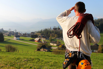 Climber in the Alps. Beautiful morning above alpine vllage