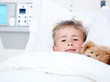 Sick adorable little boy lying in a hospital bed with his teddy