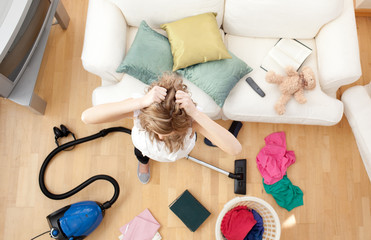 Depressed blond woman vacuuming the living-room
