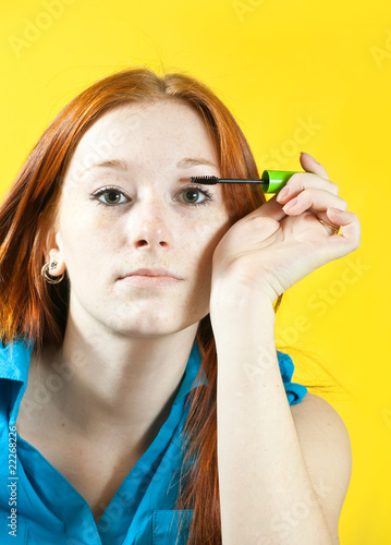 girl puts mascara on