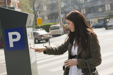 Femme payant son stationnement au parcmètre