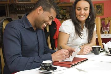 Homme signant un chèque au restaurant