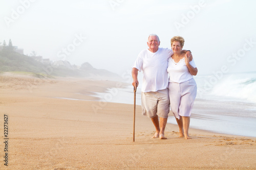 elderly couple walking on beach
