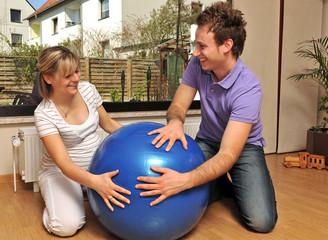 Schwangere Frau und werdender Vater mit Gymnastikball