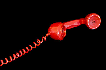 Red telephone receiver isolated on a black background