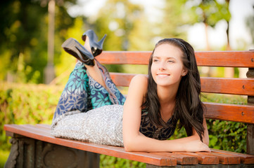 Beautiful brunette lies on bench