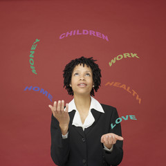 African businesswoman juggling words representing busy life