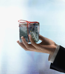 Businessman's hand holding gift box made of Euros