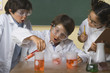 Three children doing science experiment in classroom