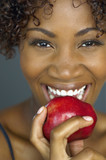 Close up of African woman eating apple